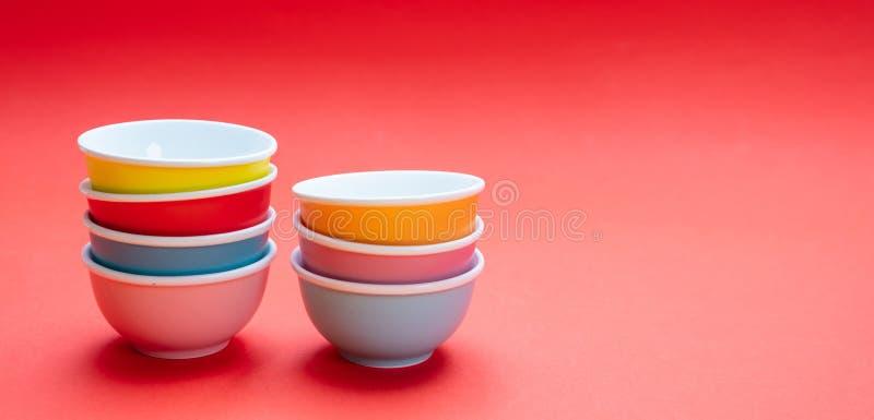 Kleurrijke schone ceramische die kommen op rode kleurenachtergrond worden gestapeld, exemplaarruimte stock afbeeldingen