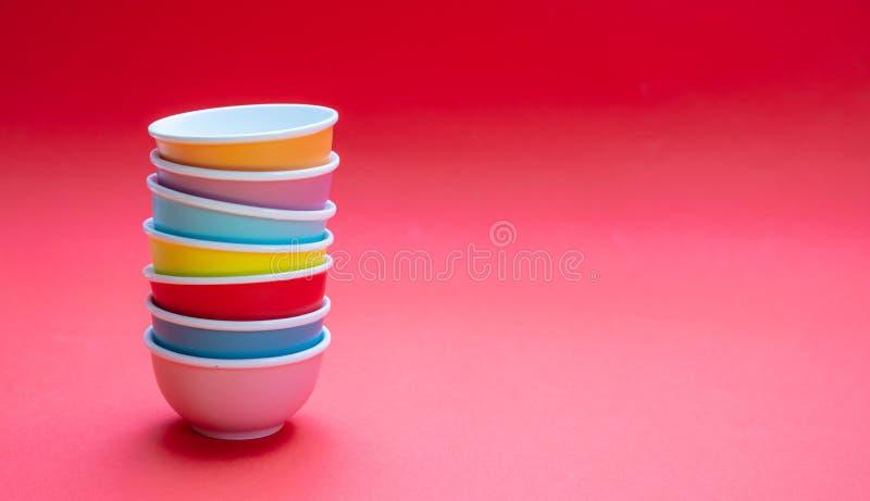 Kleurrijke schone ceramische die kommen op rode kleurenachtergrond worden gestapeld, exemplaarruimte royalty-vrije stock afbeelding