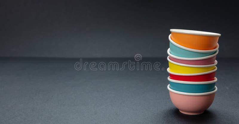 Kleurrijke schone ceramische kommen die op zwarte kleurenachtergrond worden gestapeld, exemplaarruimte royalty-vrije stock afbeeldingen
