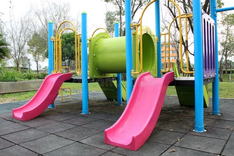 Kleurrijke speelplaats in openbare park, dia en schommeling op werfacti stock fotografie