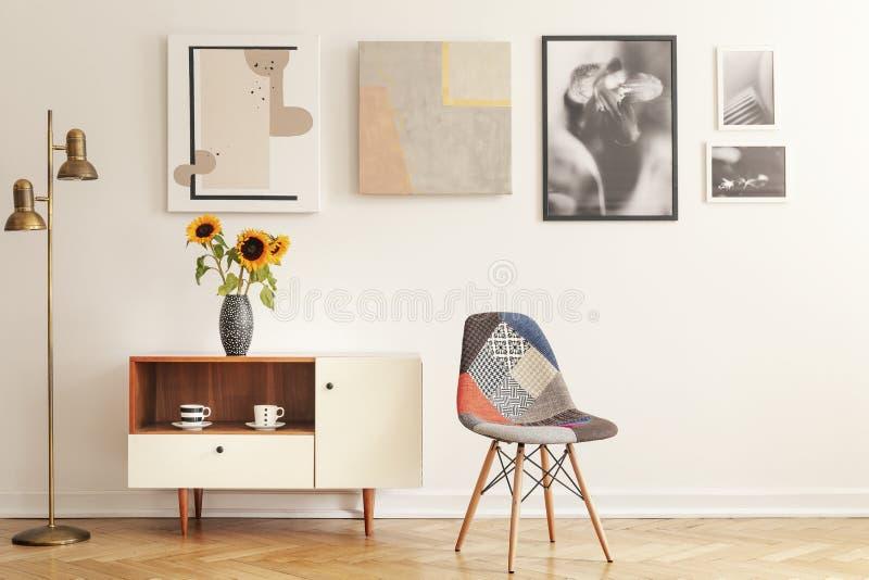 Kleurrijke stoel die zich in wit woonkamerbinnenland bevinden met galerij op muur, kast met bloemen en theekoppen stock afbeeldingen