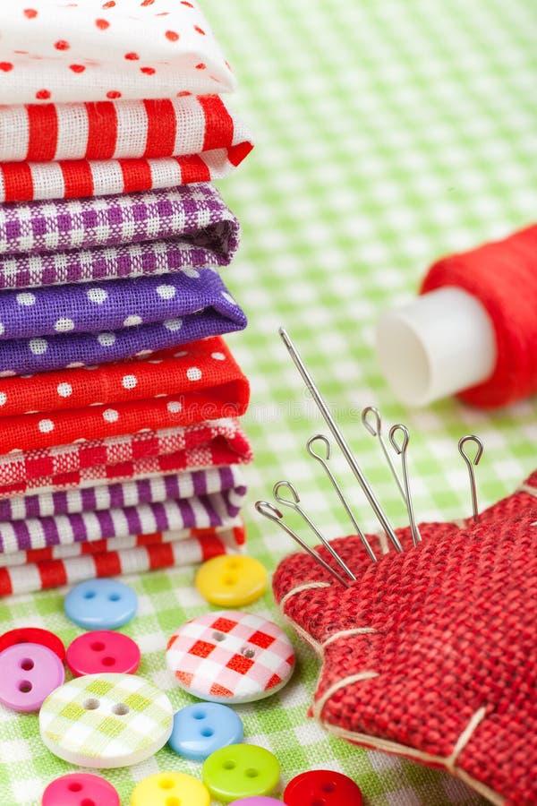 Kleurrijke stoffen, knopen, speldkussen, vingerhoedje, spoel van draad - die voor het naaien wordt geplaatst stock afbeeldingen