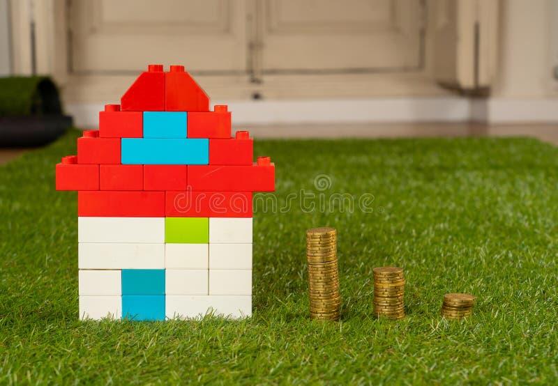 Kleurrijke stuk speelgoed huis en stapels van muntstukken op gras in hypotheekbesparingen en de industrie van de Bezitsinvesterin royalty-vrije stock afbeeldingen