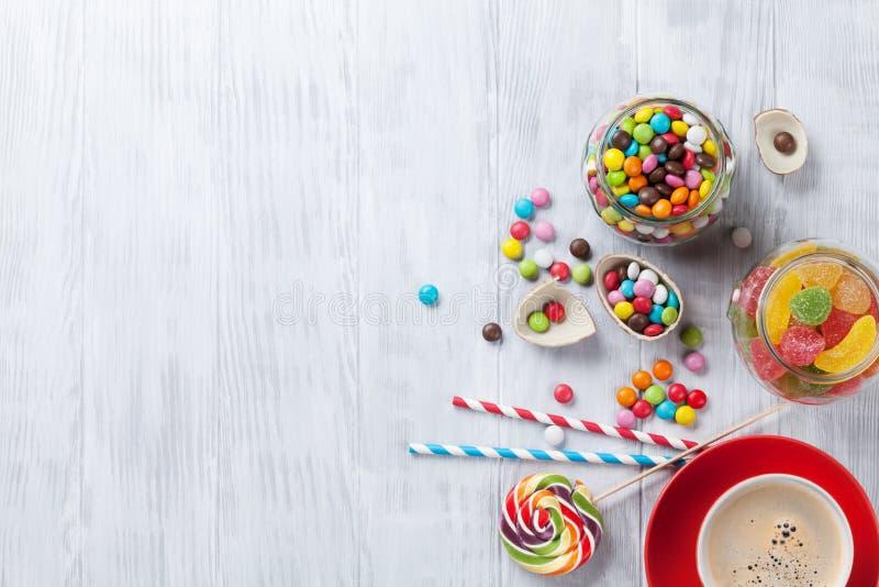 Kleurrijke suikergoed en koffie op houten lijst stock afbeeldingen
