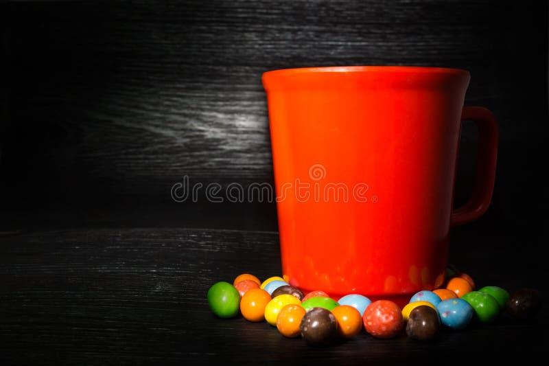 Kleurrijke suikergoedrand van rode kop op zwarte houten textuur backg stock foto's