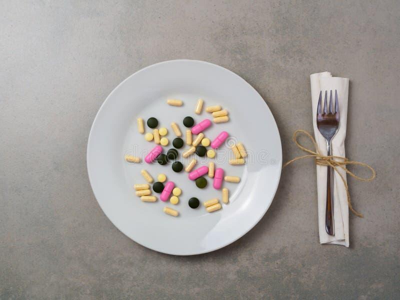 Kleurrijke tabletten op een witte schotel, hoogste mening royalty-vrije stock foto