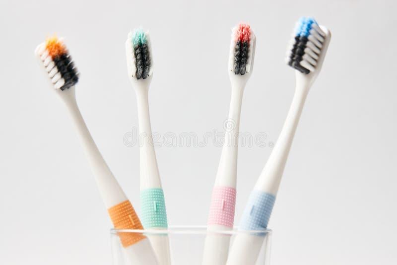 Kleurrijke tandenborstels in glas op witte achtergrond stock foto's