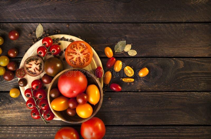 Kleurrijke tomaten op houten achtergrond Hoogste mening donkere houten lijst royalty-vrije stock foto