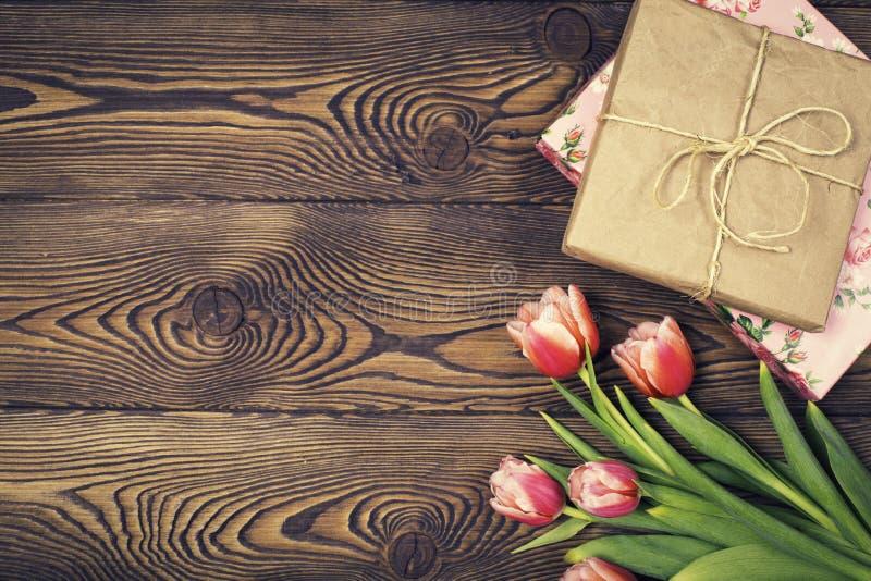 Kleurrijke tulpen en giftvakjes op houten lijst Hoogste mening met exemplaarruimte Vlak leg royalty-vrije stock fotografie