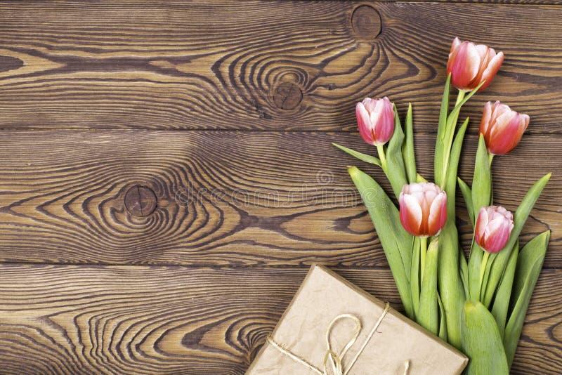 Kleurrijke tulpen en giftvakjes op houten lijst Hoogste mening met exemplaarruimte Vlak leg stock foto's