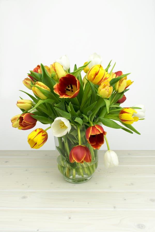 Kleurrijke tulpiabloesems op houten en witte achtergrond stock foto's