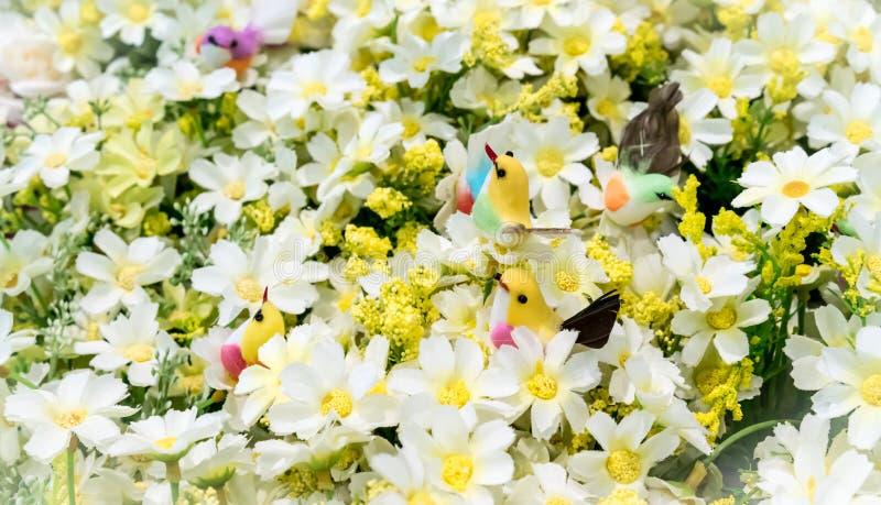 Kleurrijke valse vogels onder kunstmatige witte bloemen royalty-vrije stock afbeeldingen