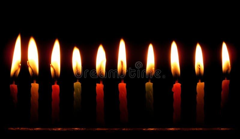 Kleurrijke verjaardagskaarsen die tegen zwarte achtergrond branden stock afbeelding