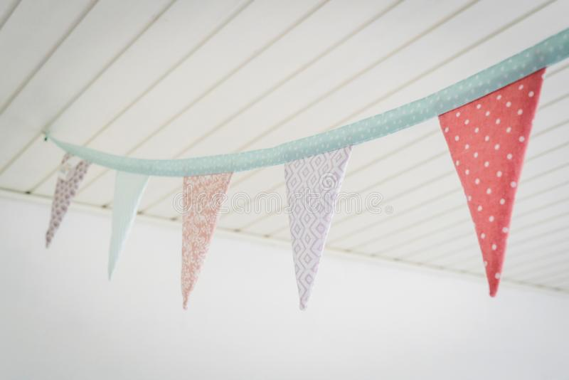 Kleurrijke verjaardagsvlaggen die in pastelkleuren van een plafond hangen royalty-vrije stock afbeelding