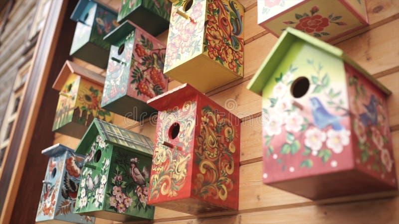 Kleurrijke vogelhuizen Met de hand gemaakt houten vogelhuis op logboekhuis Vogelhuizen op de muur buurt Houten vogelhuis binnen stock afbeeldingen