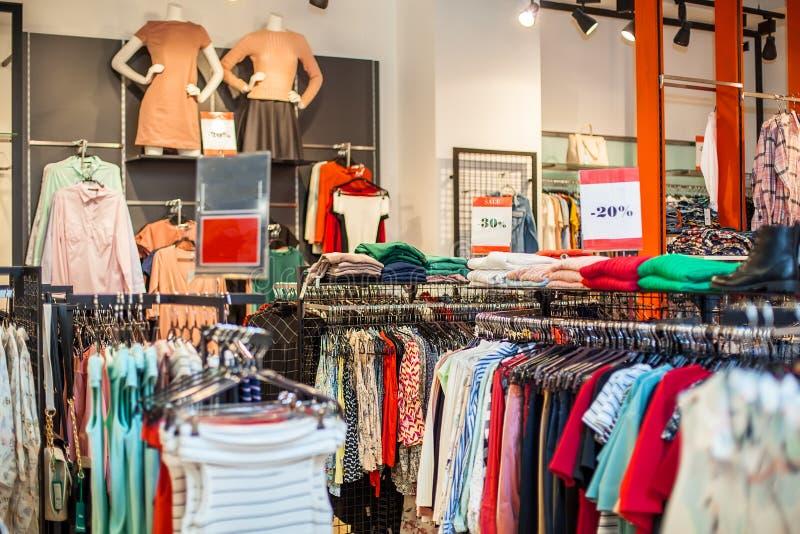 Kleurrijke vrouwen` s kleding op hangers in een kleinhandelswinkel Manier en het winkelen concept stock afbeelding