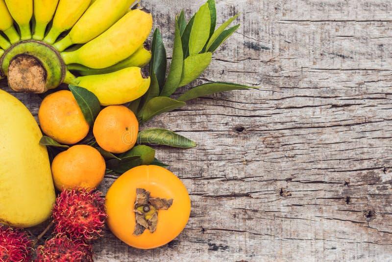 Kleurrijke vruchten op de witte houten lijst, Bananen, carambola, mango, papaja, mandarin, rambutan, Pamela, exemplaarruimte voor royalty-vrije stock afbeeldingen