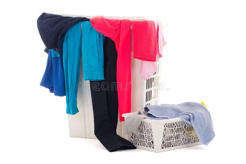 Kleurrijke vuile kleren in een wasmand op witte achtergrond stock afbeelding