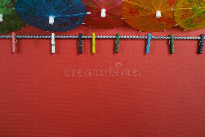 Kleurrijke washline met wasknijpers en document paraplu's, exemplaarkuuroord royalty-vrije stock fotografie
