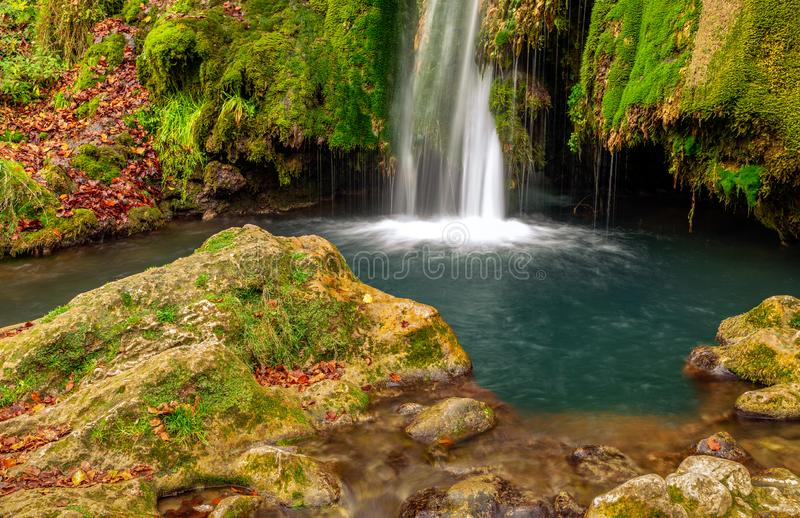 Kleurrijke waterval in de bos vroege herfst met gebladerte royalty-vrije stock foto's