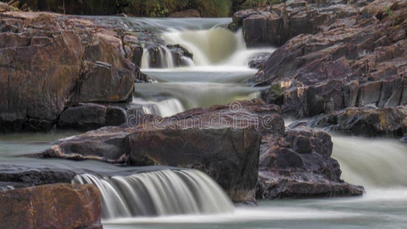 Kleurrijke Waterval rotsachtige die steengroeve door groene pogingen en geschilderde rotsen wordt omringd stock fotografie