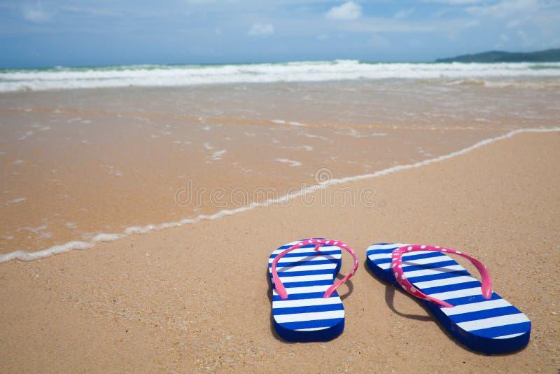 Kleurrijke wipschakeling footware op overzees strand stock afbeelding