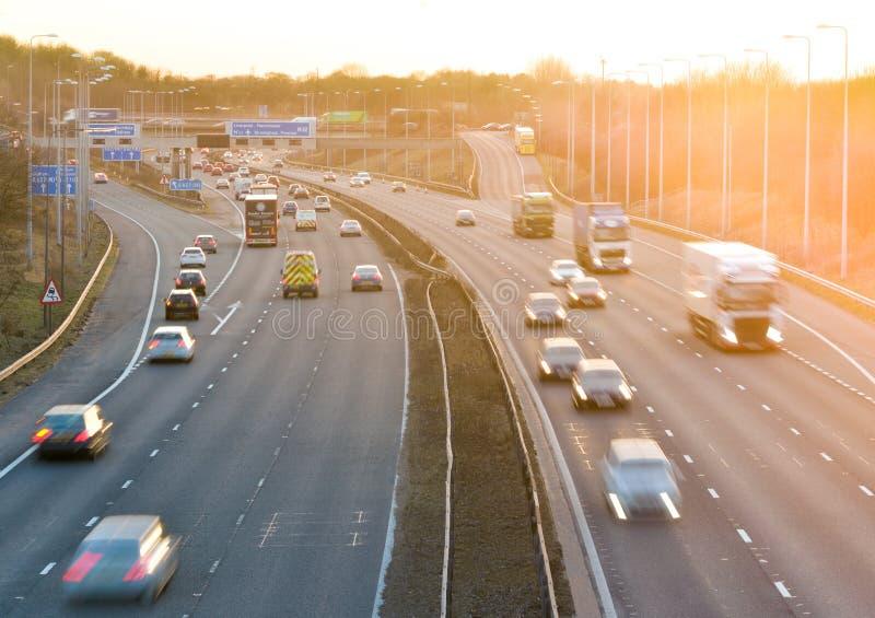 Kleurrijke zonsondergang bij M1-autosnelweg met zwaar verkeer stock afbeelding