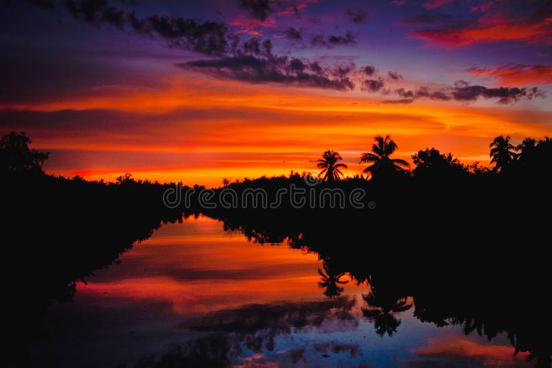 Kleurrijke zonsondergang met wolken lichte stralen over de rivier met bezinningen over het landschapsachtergrond van de silhoueta stock fotografie