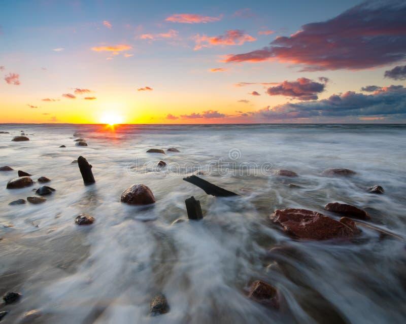 Kleurrijke zonsondergang over een overzees strand tijdens een onweer royalty-vrije stock afbeeldingen