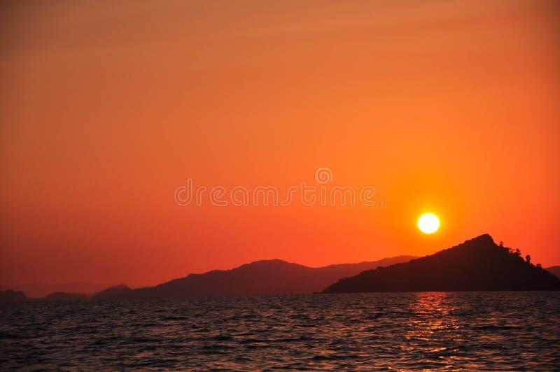 Kleurrijke zonsondergang over waterspiegel stock foto's
