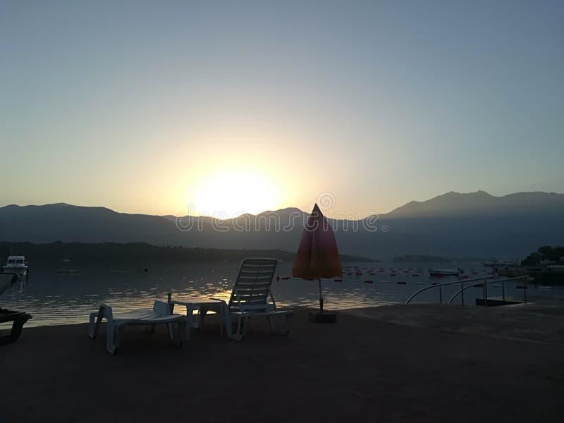 Kleurrijke zonsopgang op het strand tegen de achtergrond van het overzees en de bergen Rust op het overzees royalty-vrije stock afbeelding