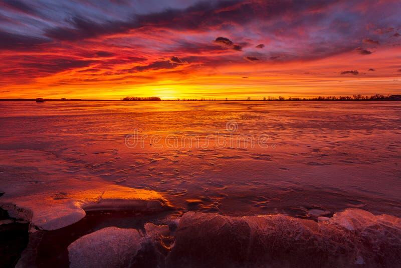 Kleurrijke Zonsopgang of Zonsondergang op een bevroren meer met rotsen royalty-vrije stock afbeeldingen