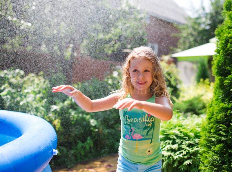 Kleuter het leuke meisje spelen met tuinsproeier Pret van het de zomer de openluchtwater in de binnenplaats stock foto's