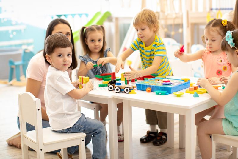 Kleuterschoolkinderen die speelgoed met leraar in speelkamer spelen bij kleuterschool Het concept van het onderwijs royalty-vrije stock foto's