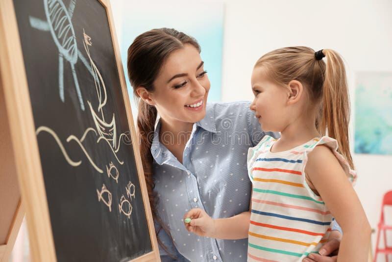 Kleuterschoolleraar en weinig kind dichtbij bord Het leren en het spelen royalty-vrije stock foto