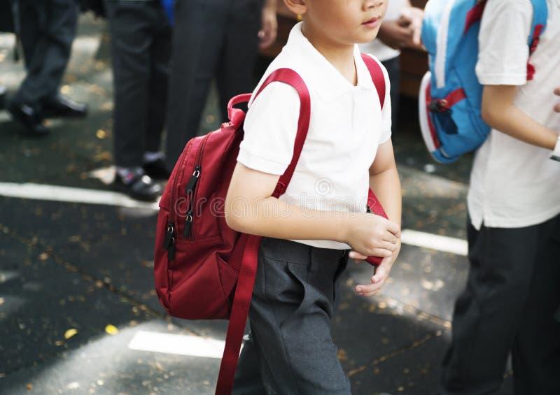 Kleuterschoolstudenten die kruisend schoolweg lopen stock afbeelding