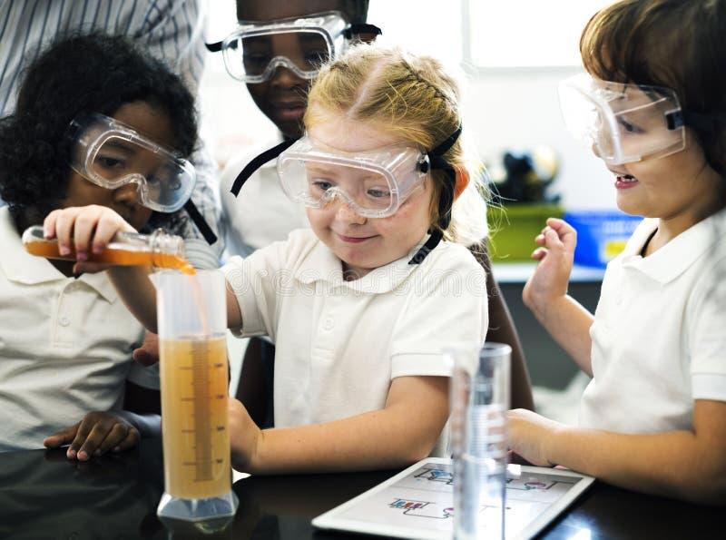 Kleuterschoolstudenten die Oplossing in Wetenschapsexperiment Labo mengen stock fotografie