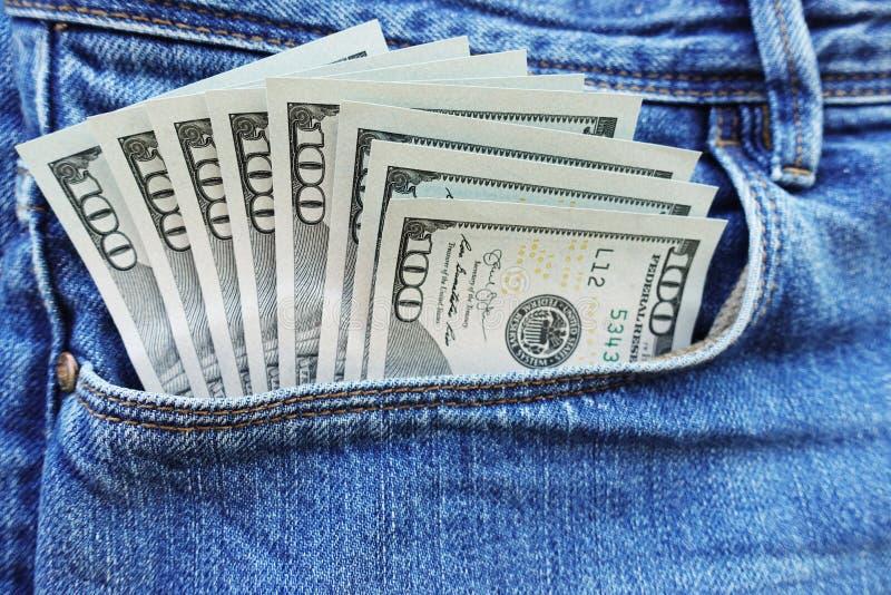 Klibba ut pengar från jeans stoppa i fickan och att spendera pengarbegrepp royaltyfri bild