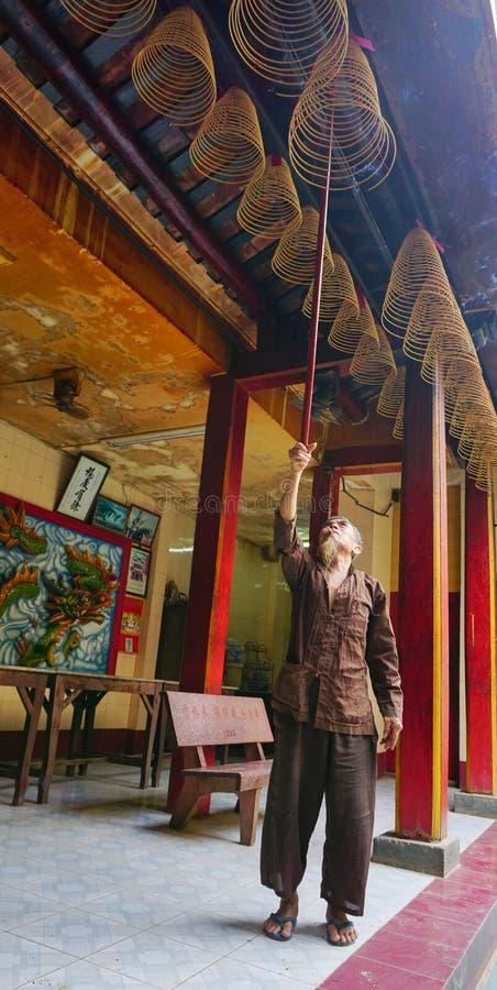 Klibbar erbjudande rökelse för den asiatiska mannen för gudarna royaltyfria foton