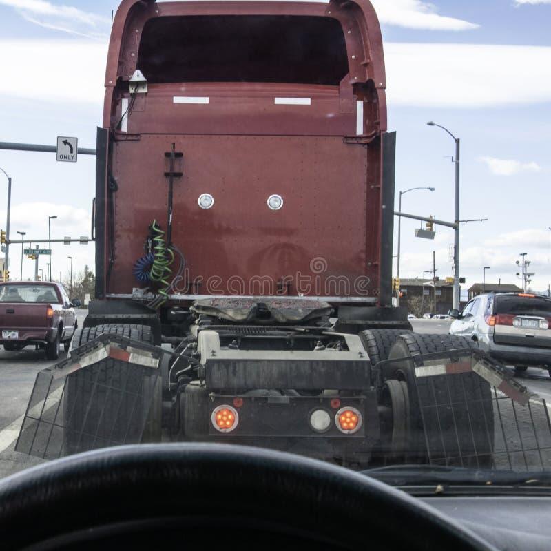 Klibbat bak en stor lastbil som är oförmögen att se signalljusen royaltyfri foto