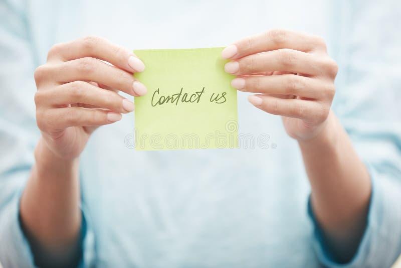 Klibbig anmärkning med kontakten oss text arkivbild