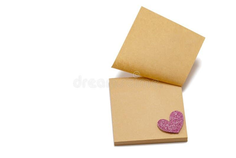 Klibbiga bruna pappers- anm?rkningar med en hj?rta P? en vit bakgrund valentin f?r dag s royaltyfri bild