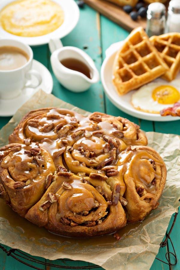 Klibbiga pecannötbullar på frukosttabellen royaltyfri bild
