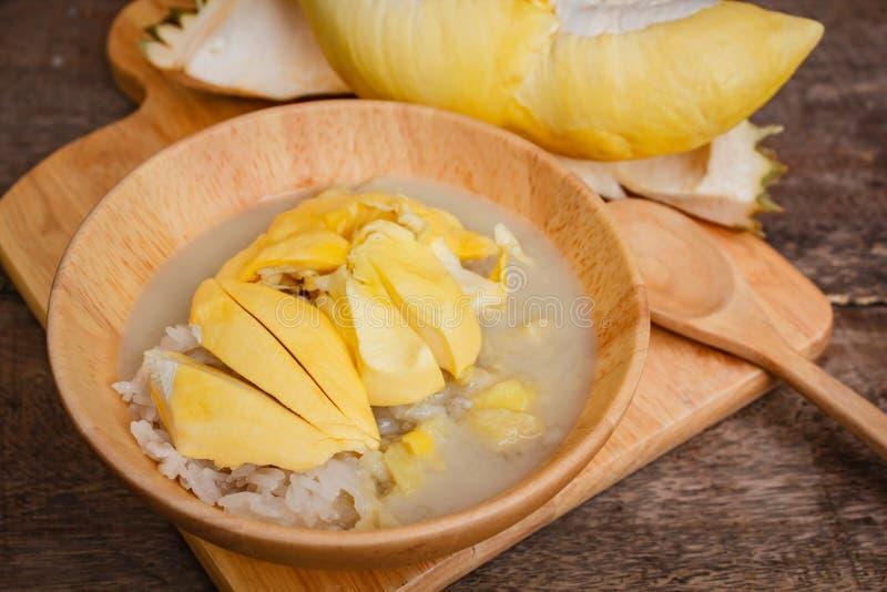 Klibbiga ris med durianen och kokosnöten mjölkar sås fotografering för bildbyråer