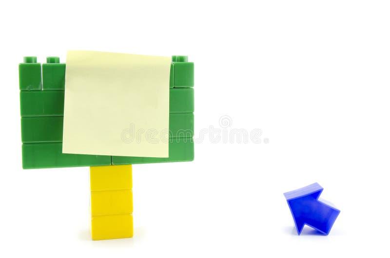 klibbigt papper över plast- signage för byggnadskvarter och blåttpilsymbol som isoleras på vit bakgrund royaltyfri foto