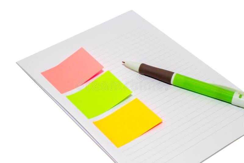 Klibbigt papper med tomt omr?de f?r text eller meddelande, ?ppnad anteckningsbok och penna bredvid isolerat arkivbild