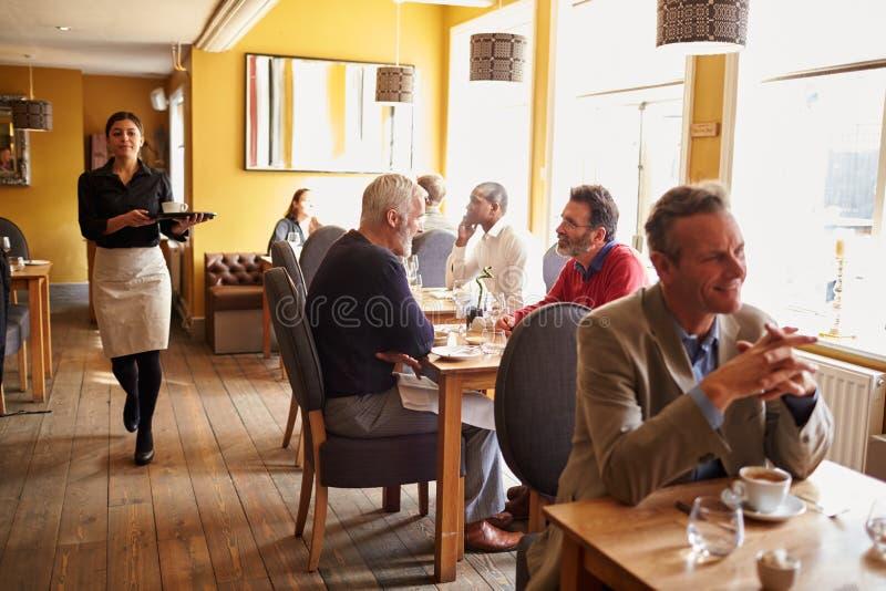 Klienci przy stołami i kelnerką w ruchliwie restauracyjnym wnętrzu obraz royalty free