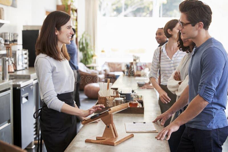 Klienci stać w kolejce rozkazywać i płacić przy sklep z kawą fotografia royalty free