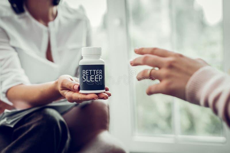Klient av den bärande cirkeln för terapeut som tar piller för bättre sömn arkivbild