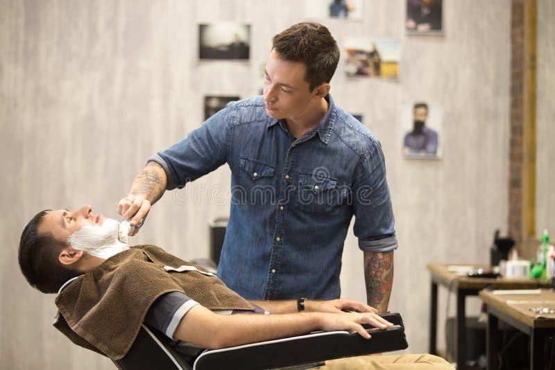Klient dostaje brody golenie w fryzjera męskiego sklepie fotografia stock